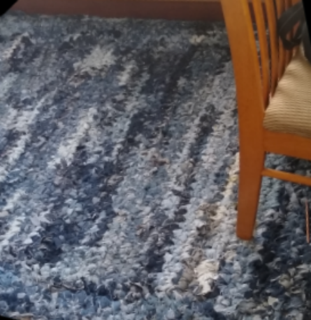recycled denim crocheted rag rug on the floor with a chair sitting on top