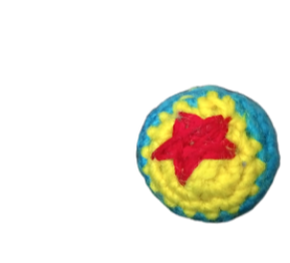 crocheted toy story luxo ball, blue and yellow with a red star, next to a dime.