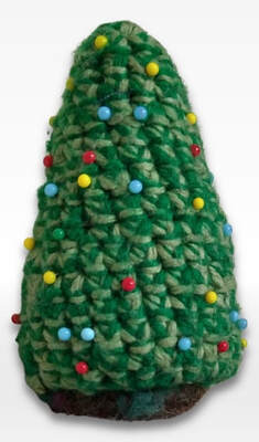 crocheted pincushion shaped like a christmas tree with pins as the ornaments