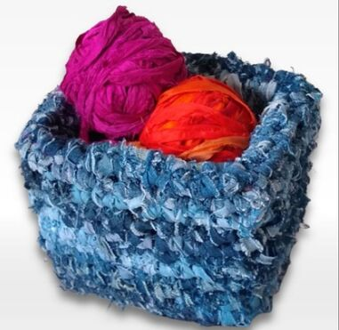 recycled denim storage basket with two balls of bright colored yarn inside of it