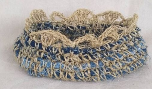 a recycled denim basket made with sisal rope crocheted around it