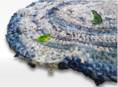 crochet rug that has wavy edges. It does not lay flat. there are two small frogs sitting on the rug